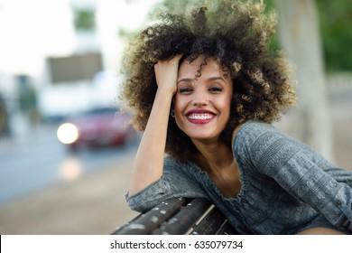 Joven mujer mixta con peinado afro sonriendo en el fondo urbano. Chica negra con ropa casual.