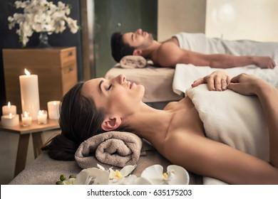 Hombre joven y mujer acostada en camas de masaje en el lujoso spa asiático y centro de bienestar
