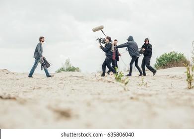 舞台裏。屋外の場所で映画のシーンを撮影する撮影クルーチーム。グループシネマセット
