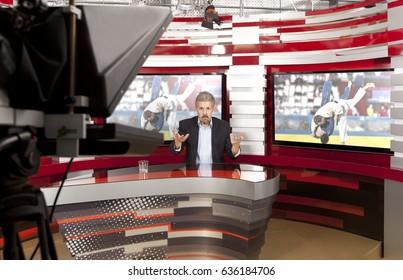 スポーツニュース。生放送中のスタジオのテレビアンカーマン