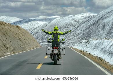 Mannen staan op motor tijdens het rijden en vrije handen in de sneeuwmoutain, Sichuan, China