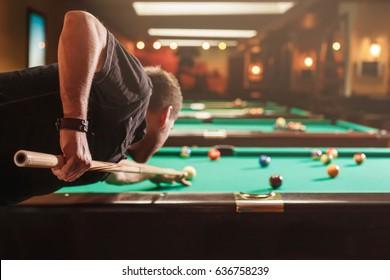 Hombre tratando de golpear la bola de billar. Sala de billar al fondo.