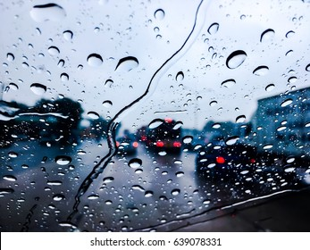 Close-up raindrops from the windshield,Dark cloud, an heavy raining.  The road are wet. To be safe,  slowly and carefully on driving.