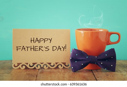 Cup of coffee with bow tie on wooden table. Father's day concept