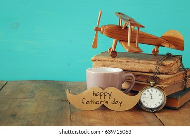 Cup of coffee with vintage father's accessories on wooden table. Father's day concept
