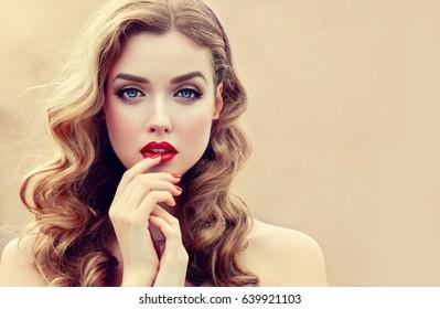長い巻き毛の美しいブロンドモデルの女の子。髪型波状カール。赤い唇と爪のマニキュア。ファッション、美容、メイクアップポートレート