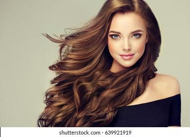 長くて光沢のあるウェーブのかかった髪のブルネットの女の子。巻き毛の美しいモデル。