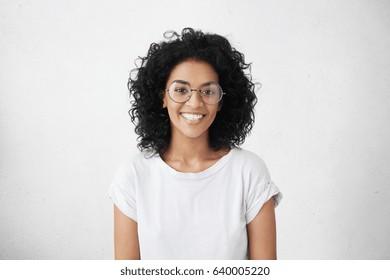 毛むくじゃらの髪型が元気に笑みを浮かべて美しいブルネットの若い浅黒い女性の屋内ポートレート