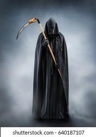 夜、霧の中に立つ死神。シルエットに大きな鎌を持っている死の擬人化の写真。