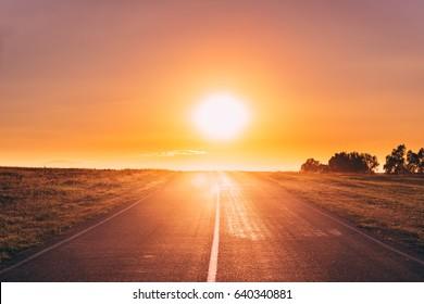 Východ slnka nad asfaltovou krajinou otvorená cesta v slnečné ráno alebo večer. Otvorená cesta v Európe v lete alebo v jesennej sezóne pri slnečnom západe alebo východe slnka