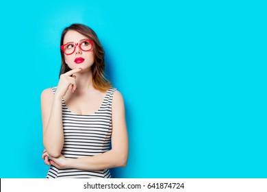 素晴らしい青いスタジオの背景にメガネで美しい若い女性の肖像画