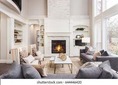 Mooie woonkamer interieur met hardhouten vloeren en open haard in nieuwe luxe woning. Grote rij ramen verwijzen naar het buitenaanzicht