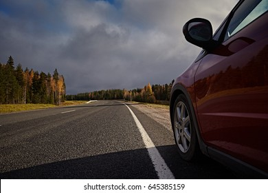 Red car on asphalt road for trip. Close-up with a wheel near a line of a marking.