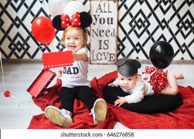 Sisters are playing with black, white and red balloons