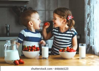 Niños felices niña y niño hermano y hermana comiendo fresas con leche