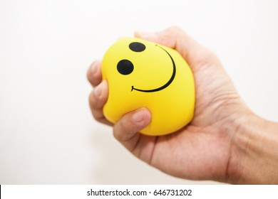 Apriete a mano la bola amarilla de estrés, sobre fondo blanco, manejo de la ira, conceptos de pensamiento positivo