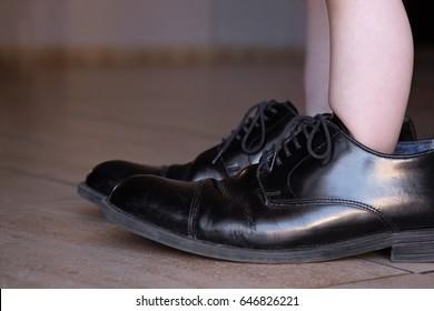 Ambitieus jong kind staat in vaders enorme zakelijke schoenen met veel ruimte over