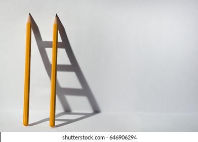 Dos lápices y una sombra en forma de escalera. Concepto de negocio de éxito, trabajo en equipo y resolución de problemas. Copie el espacio para el texto.