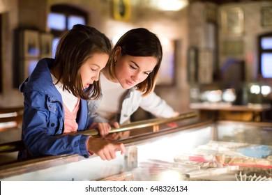 Glückliche Mutter und Tochter erforschen Ausstellungen vergangener Jahrhunderte im Museum