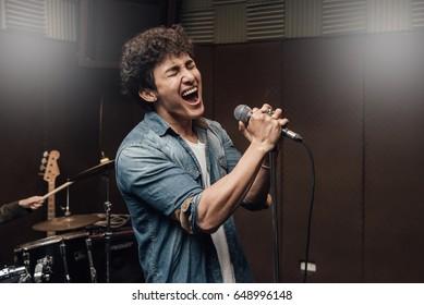 楽器のバックグラウンドを持つスタジオで歌う男性のリードボーカル。