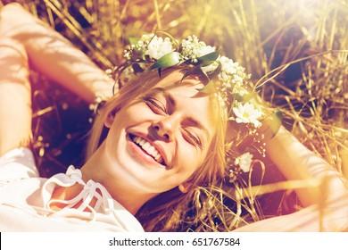 自然、夏休み、休暇、人々の概念-わらの上に横たわる花の花輪で幸せな笑顔の女性