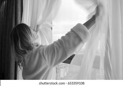 白いローブを着た大人の若い女性がカーテンを開き、窓に立っています
