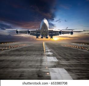 Un avión de pasajeros volando en el colorido cielo del atardecer. El avión despega de la pista del aeropuerto. Vista frontal del avión.