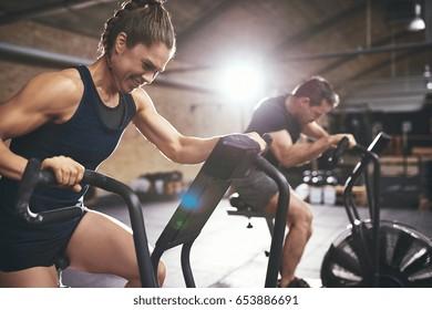 広々としたライトジムで設備を使い、ほとんど運動しないスポーティーな男女。