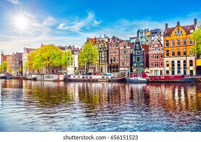 Amsterdam Niederlande tanzen Häuser über Fluss Amstel Wahrzeichen in alten europäischen Stadt Frühlingslandschaft.
