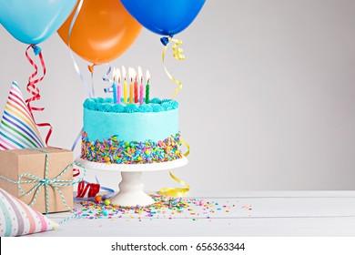 Pastel de cumpleaños azul, regalos, sombreros y globos de colores sobre gris claro.