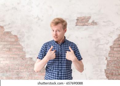 困惑したことの言い訳をしている若い男の肖像画。白い背景の上の人間の顔の表情、感情、不信感、感情の概念