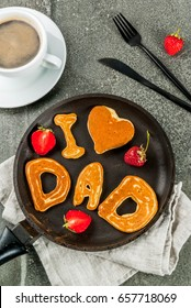 Celebrating Father's Day. Breakfast. The idea for a hearty and delicious breakfast: pancakes in form of congratulations - I love dad. In a frying pan, coffee mug and strawberries. Top view copy space