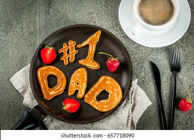 Celebrating Father's Day. Breakfast. The idea for a hearty and delicious breakfast: pancakes in form of congratulations - #1 dad. In a frying pan, coffee mug and strawberries. Top view copy space