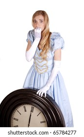A woman dressed in a cinderella dress holding up a big clock scared to know that it is midnight.