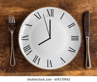 Concepto de ventana de alimentación de ocho horas o tiempo del desayuno con reloj en el plato y cuchillo y tenedor en la mesa de madera, vista aérea