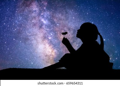 Silhouette of little girl holding a flower at the stars background