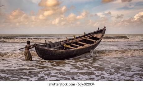 漁師は、日没時にインドの西ベンガル州タージプルのビーチで、噴出する海の波とボートのバランスをとろうとします。