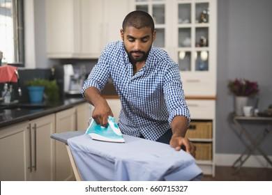自宅の家庭の台所で布にアイロンをかける若い男
