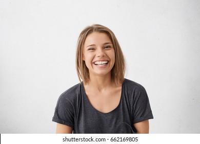 屋内で楽しんでいる彼女の完璧な歯を見せて幅広い笑顔で笑って非常に喜んでいる短い金髪の魅力的な女性。結婚するよう提案された後、喜んで興奮して陽気なフェムレ