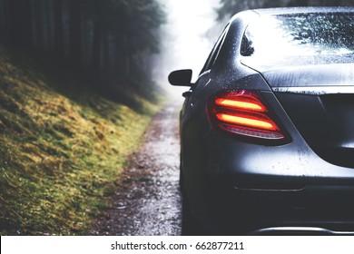 モダンなデザインのヘッドライトを備えた雨滴車によって合理化された美しい。シルバーグレーカラーの豪華なビジネスクラスの自動車。スタイリッシュなレンタル車。旅行の気象条件、コピースペース
