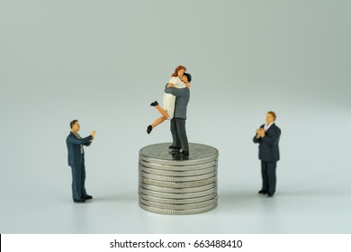 La gente miniatura con la pareja que se coloca en la pila superior de monedas y otras que aplauden con el fondo blanco como éxito aman concepto de la vida.