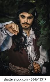 Retrato de hombre en traje de pirata posa al aire libre.