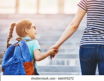 Padres y alumnos de primaria van de la mano. Mujer y niña con mochila detrás de la espalda. Comienzo de clases. Primer día de otoño.