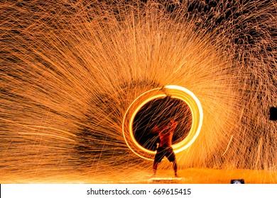 Feuertänzer schwingen Feuertanzshow Feuershow auf dem Strandtanzmann, der mit Feuer jongliert, Koh Samet, Thailand