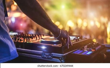 DJ Mischen im Freien beim Beach Party Festival mit Menschenmenge im Hintergrund - Sommer Nachtleben Blick auf Disco Club draußen - Weicher Fokus auf Hand - Spaß, Jugend, Unterhaltung und Fest Konzept