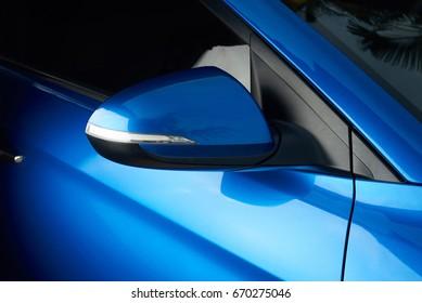 Side car mirror close-up. Details of blue car