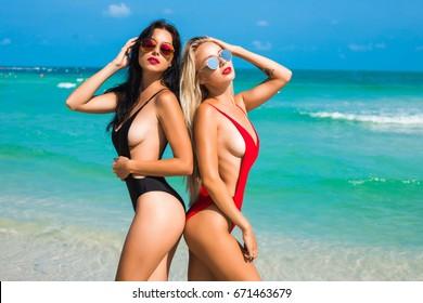 ビーチで美しい2つの美しい日焼けしたセクシーな女の子、ブロンドとブルネット、長い髪、完璧なスポーツの数字、トレンディな赤と黒の水着、サングラス、熱帯の島でのリラクゼーション、夏