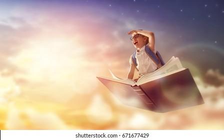 ¡De vuelta a la escuela! Feliz niño trabajador lindo volando en el libro sobre fondo de cielo al atardecer. Concepto de educación y lectura. El desarrollo de la imaginación.