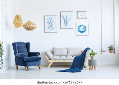 Sofá blanco y sillón azul en la sala de estar con carteles en la pared