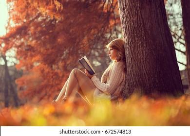 Hermosa joven morena sentada en un otoño las hojas caídas en un parque, leyendo un libro